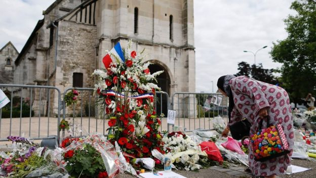 A Muslim woman lays tribute to a murdered Catholic priest