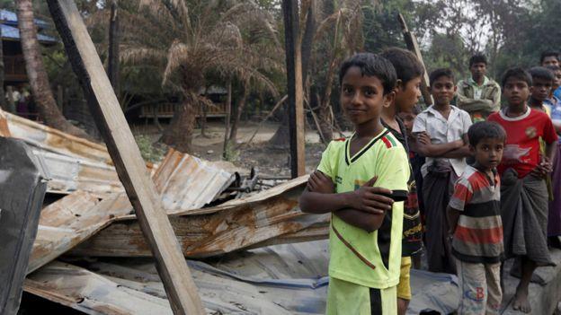 Niños rohingya frente a una casa destruida