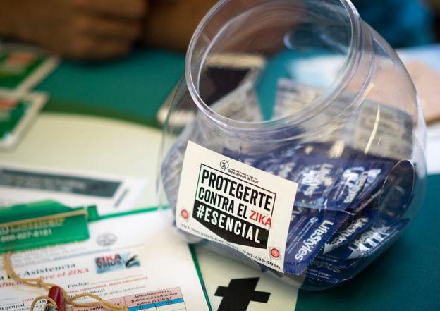 Bote con preservativos con una pegatina que anima a usarlos para protegerse contra el virus del zika.