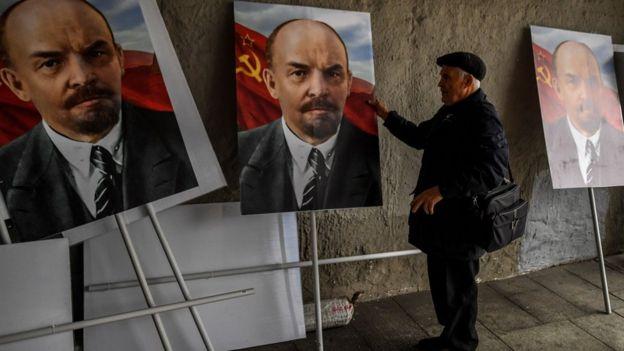 A man examines three colour portraits of Vladimir Lenin