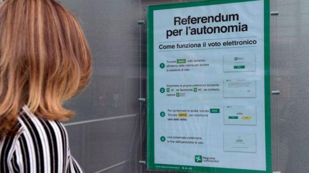 Una mujer observa un letrero sobre el referendo por la autonomía.