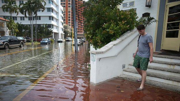 Hombre saliendo de un edificio en una calle inundada