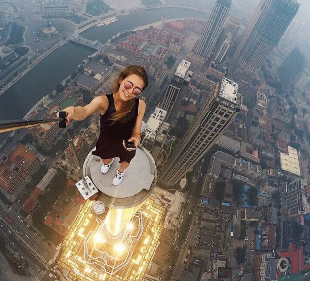 Angela Nikolau holding a selfie-stick on a small platform with the ground hundreds of metres below her