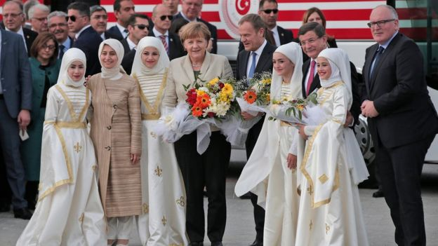 German Chancellor Angela Merkel, centre, accompanied by EU Council President Donald Tusk, centre right, Turkish Prime Minister Ahmet Davutoglu, 2nd right, and EU Commission Vice President Frans Timmermans, right, pose for pictures during a visit at the Nizip refugee camp in Gaziantep province.
