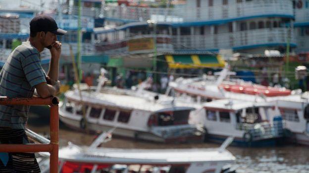 Joven mirando los barcos en el puerto de Manaos.