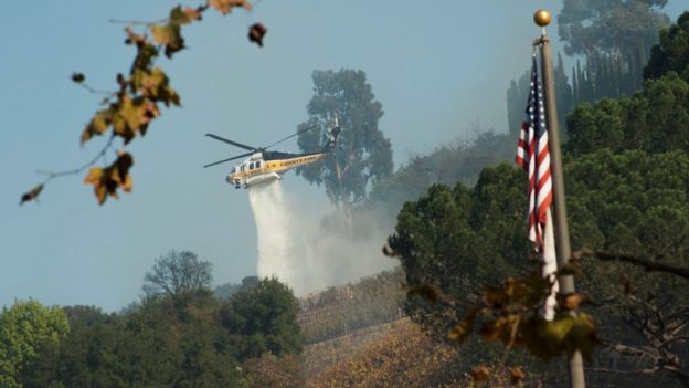 A helicopter drops water on a vineyard owned by Rupert Murdoch damaged by the Skirball fire near the Bel Air neighbourhood on the west side of Los Angeles