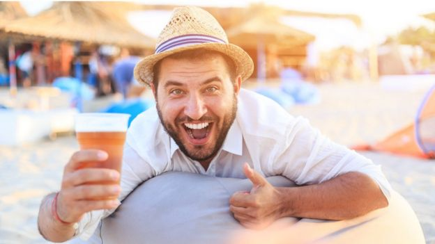 Man with beer on beach