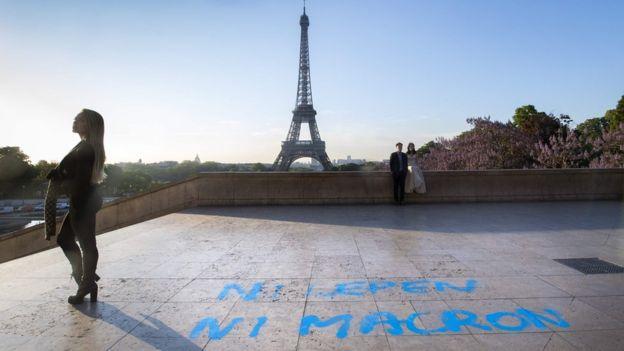 İnsanlar, Fransa'daki cumhurbaşkanlığı seçimlerinde ikinci tura atıfta bulunan bir grafiti yerinde olan Trocadero plazasında Eyfel Kulesi'nin önünde resim çekiyorlar.