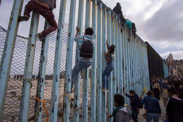 Pessoas sobre a cerca de separa México e Estados Unidos