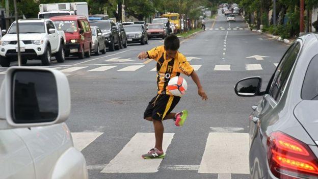 Un niño jugando con un balón en una calle de Asunción