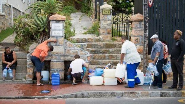 Personas hacen fila para recoger agua de una fuente en Ciudad del Cabo.