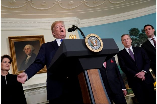 U.S. President Donald Trump, flanked by Lockheed Martin CEO Marillyn Hewson, U.S. Trade Representative Robert Lighthizer and White House Homeland Security Advisor Tom Bossert, delivers remarks before signing a memorandum on intellectual property tariffs on high-tech goods from China, at the White House in Washington, U.S. March 22, 2018. REUTERS/Jonathan Ernst