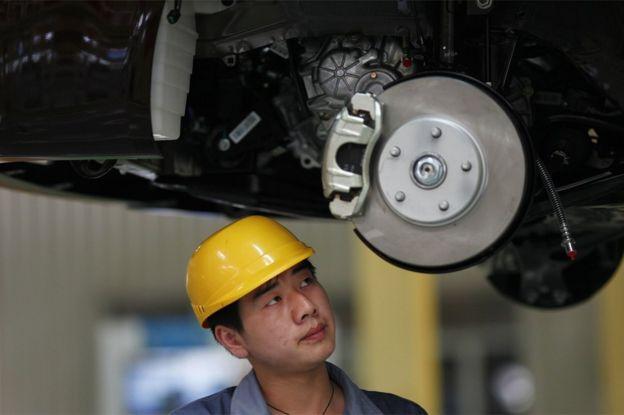 Un empleado mira a un vehículo en proceso de ensamblaje en la planta de Geely en Cixi, en la provincia china de Zhejiang, el 21 de junio de 2012.