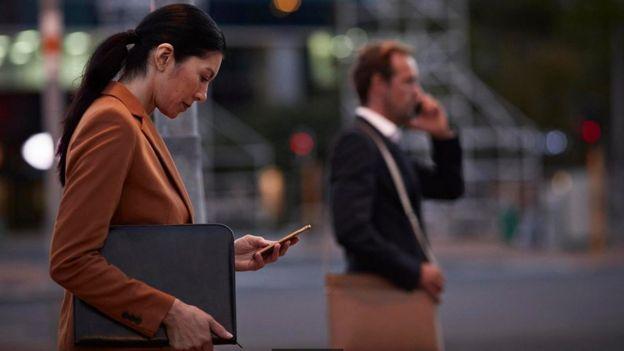 Dos personas vestidas con traje cruzando una calle, con sus teléfonos en la mano