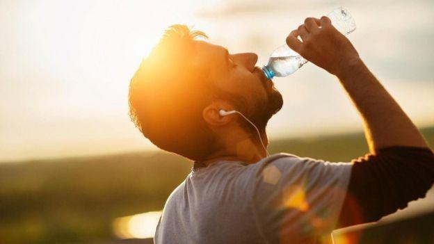 شاب يشرب المياه بعد ممارسة الرياضة