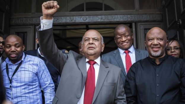 Former South African Finance Minister Pravin Gordhan raises his fist as he addresses a group of supporters outside the South African National Treasury in Pretoria