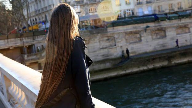 Jovem no sol às margens do Sena, em Paris