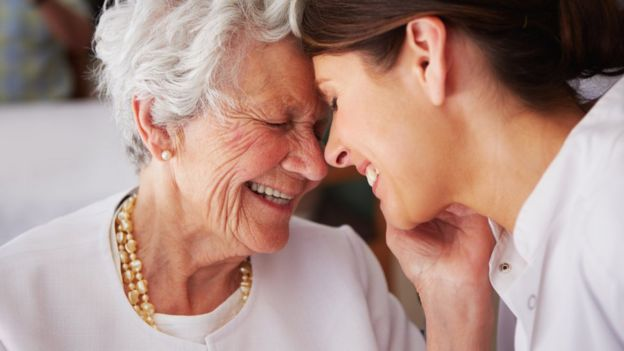 Elderly woman with girl smiling.