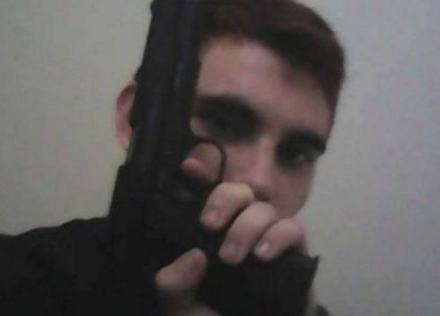 Nikolas Cruz, holding a gun in front of his face