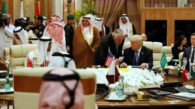 US Secretary of State Rex Tillerson (standing) hands President Donald Trump a note at a Gulf Co-operation Council summit in Riyadh, Saudi Arabia (21 May 2017)