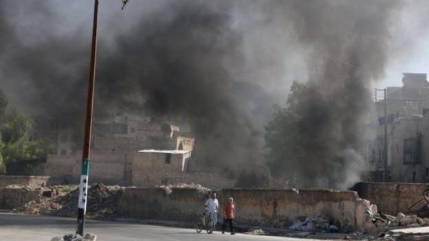 Men walk past burning tyres, which activists said are used to create smoke cover from warplanes, in Aleppo