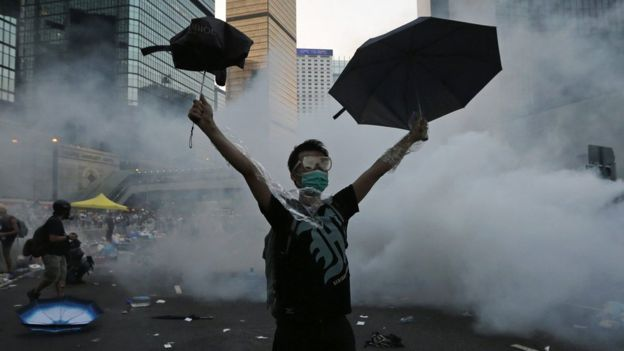 A protester raises an umbrella during demonstrations outside the government headquarters in Hong Kong, 28 September 2014