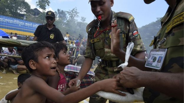 Bangladeshi soldiers distribute rice to young Rohingya refugees at the camp of Balukhali near Gumdhum on September 25, 2017