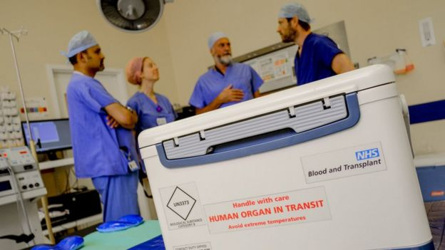 An organ in transit in a hospital room filled with doctors. Image copyright NHSBT