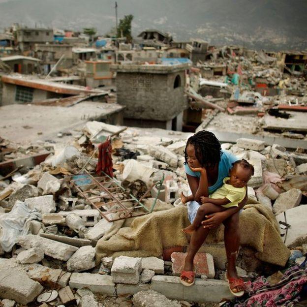 Mujer con bebé sentada sobre las ruinas de lo que era su casa antes del terremoto de 2010 en Haití.