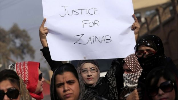 Women demonstrate, holding a sign saying Justice For Zainab, in Kasur, Pakistan