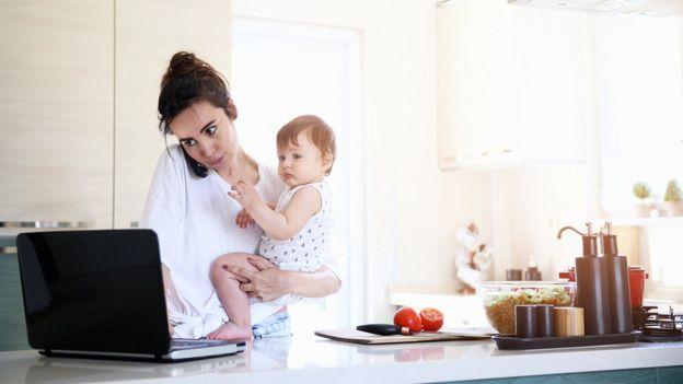 Mãe trabalhando com bebê no colo