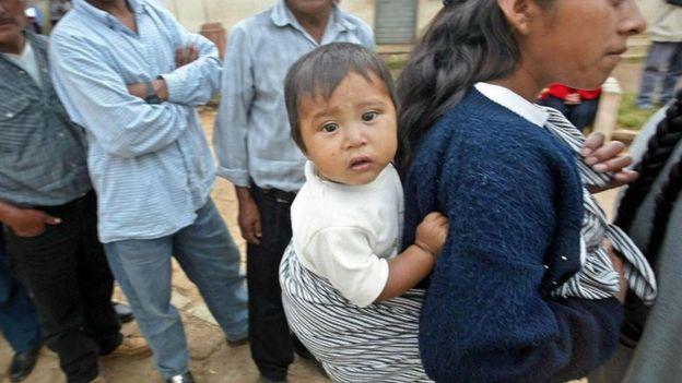 Una joven con un bebé en su espalda