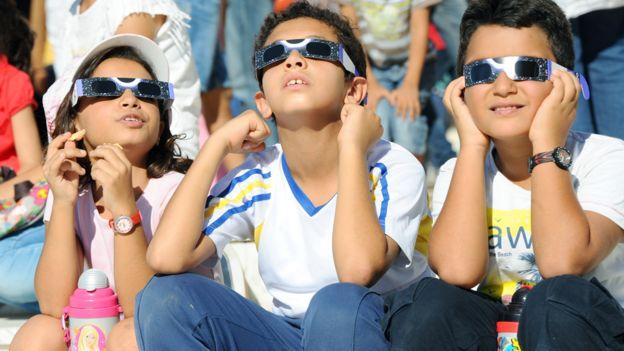 Niños viendo un eclipse con lentes especiales