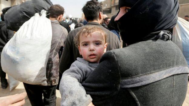 Mulher síria carrega bebê caminhando para fora de Ghouta oriental