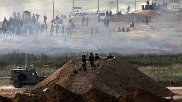 Israeli soldiers stand on a berm near the Israel-Gaza border fence, as Palestinians protest on the other side (6 April 2018)