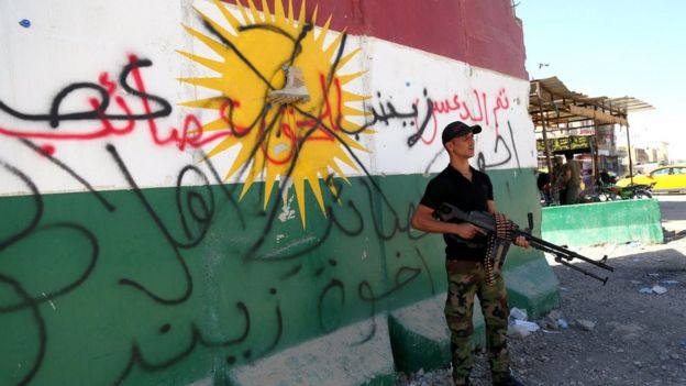 A Shia militiaman stands next to a crossed-out Kurdish flag in Tuz, south of Kirkuk city, Iraq (17 October 2017)