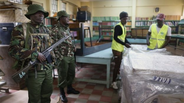 Electoral agents work to unpack electoral materials to be distributed to smaller polling stations, as police officers keep an eye on them at a tallying centre in the capital Nairobi, on 7 August 2017, a day before the country's general elections