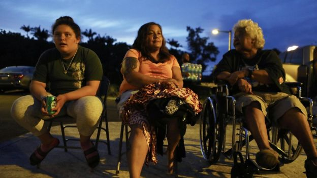 "Evacuees (L to R) Anastasia de Sousa, Nina Bermasina and Aunty Willy Kamalamalama de Sousa sit outside the emergency shelter where they are staying at the Pahoa Community Center on Hawaii""s Big Island on May 5, 2018 in Pahoa, Hawaii."