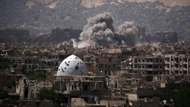 Humo saliendo de un edificio en un distrito controlado por rebeldes en Damasco, luego de un ataque aéreo.