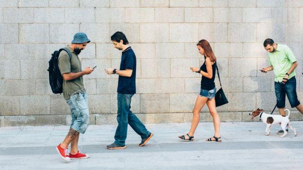personas caminando con celular