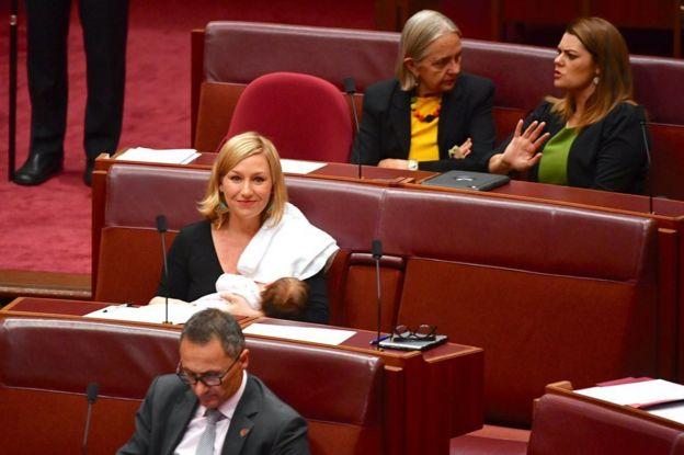 A ex-senadora Larissa Waters ao amamentar no parlamento da Austrália em maio