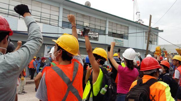Equipo de rescatistas y voluntarios al lado del edificio derrumbado.