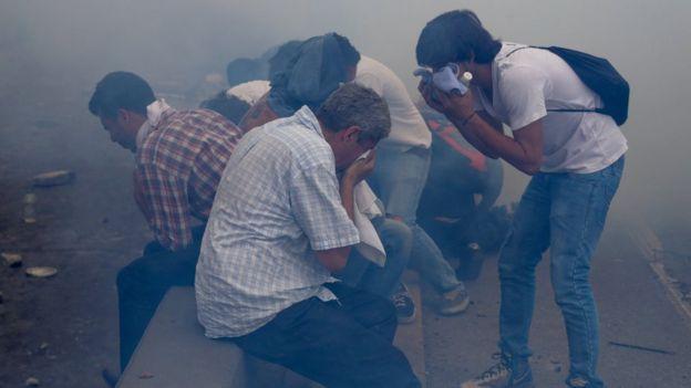 Manifestantes afectados por los gases lacrimógenos durante las protestas opositoras en Caracas.