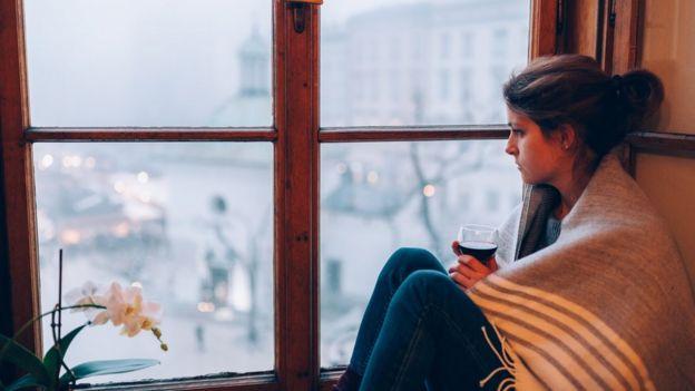 Mujer mirando por la ventana