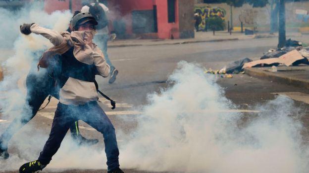 Joven devuelve un gas lacrimógeno a la policía.