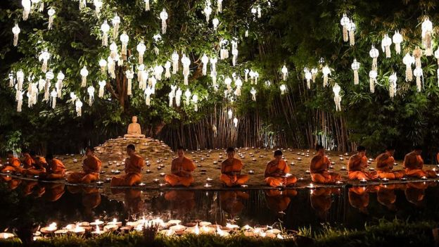 Novice Buddhist monks sit to pray at Wat Phan Tao temple to mark the beginning of the annual Yi Peng festival in the popular tourist city of Chiang Mai in the north of Thailand
