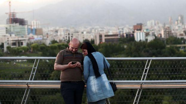 Una pareja de iraníes con un teléfono en Teherán