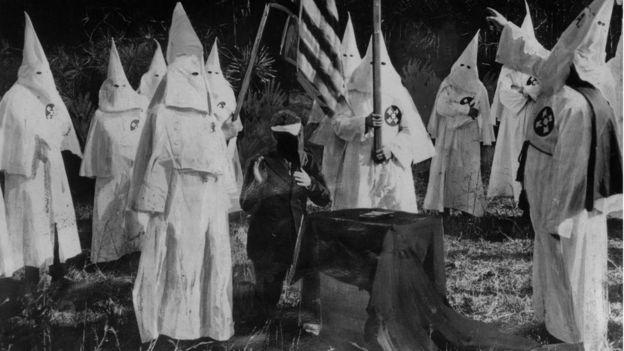 Iniciação de novo membro da Ku Klux Klan - 10 pessoas com vestes da Ku Klux Klan e um homem de terno sentado, rosto coberto, mão para cima em juramento