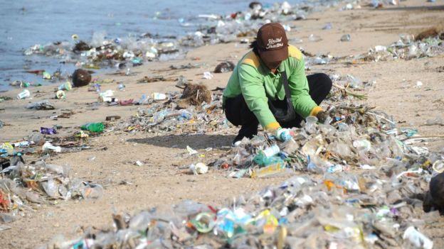 Person collecting rubbish at Kuta beach