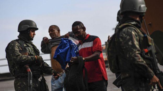 Soldados revistam moradores do Morro do Macaco, no Rio